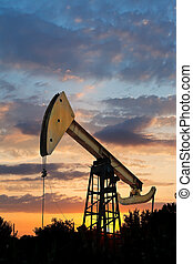 oil extraction by pumpjack in Caucasus region at summer sunset
