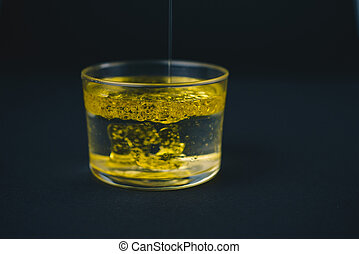 Oil falling on water in a low glass with drops of oil on the bottom