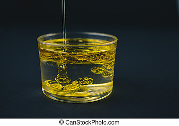 Oil falling on water in a low glass with drops of oil on the bottom.