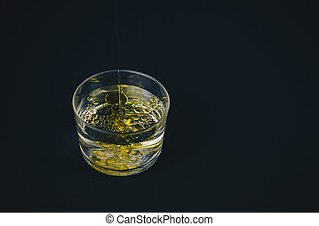 Oil falling on water in a low glass with drops of oil on the top