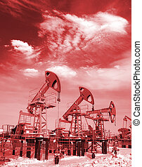 Oil and gas industry. Work of oil pump jack on a oil field. White clouds above oil field. Red filter