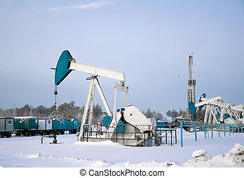 Oil Field - oil pumps and drilling rig in the winter. Russia...