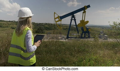 Oil forewoman engineer using a tablet pc to check...