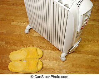 Oil heater and plush slippers on the parquet floor. Can be a suggestion for comfort idea.