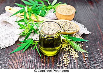 Oil hemp in jar with flour and grain on wooden board