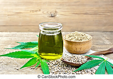 Oil hemp in jar with flour in bowl on wooden board