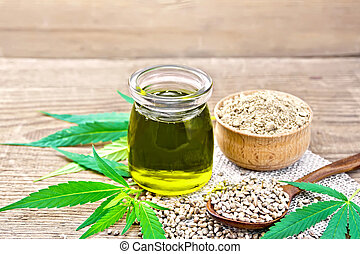 Oil hemp in jar with flour in bowl on wooden table