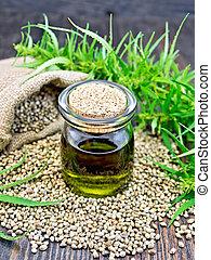 Oil hemp in jar with seed on dark board