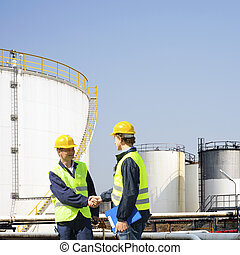 Oil industry - Two oil industry workers shaking hands in...