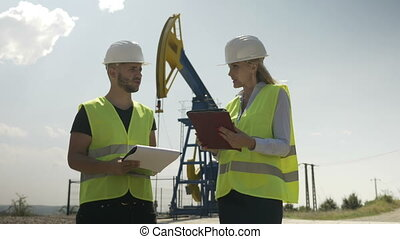 Oil industry supervisors controlling the operation of oil...