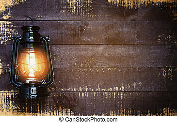 Oil lamp at night on a wooden wall - old Lantern vintage classic black