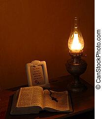 Oil Lamp Light - A lit oil lamp on an old school desk by an...