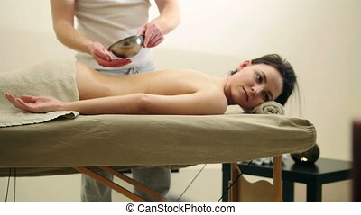 Oil massage for back. Relaxation treatment for young female, slider