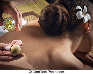 oil massage fragment of young beautiful woman in spa environment.