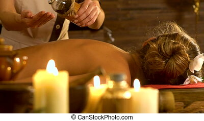 Oil massage pouring in hands .Woman lying on wooden massage...