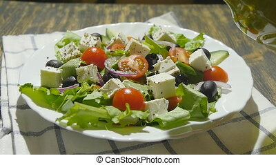 oil pouring into bowl of greek salad