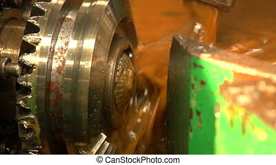 Oil pours on a turning cogwheel with some cutting device nearby in a workshop