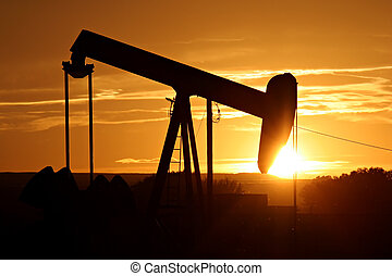 oil pump silhouette against a bright orange sky