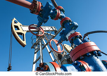 Oil pump, industrial equipment on sunset sky background. Rocking machines for extraction of oil. Mining. Petroleum concept.