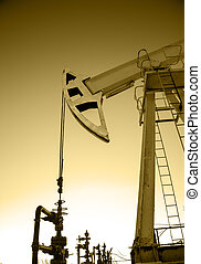 Oil pump jack and wellhead in the oilfield. Oil and gas...
