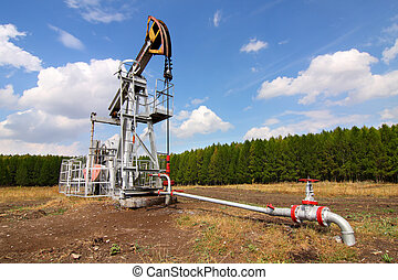 Oil pump jack - Grey oil pump jack on field and blue sky.
