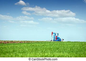 oil pump jack on green field