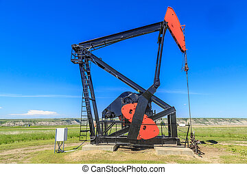 Oil Pump Jack - Single working oil pump jack on a sunny day...