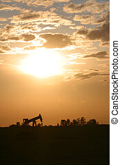 oil pump jack - An oil pump jack is silhouetted by the...