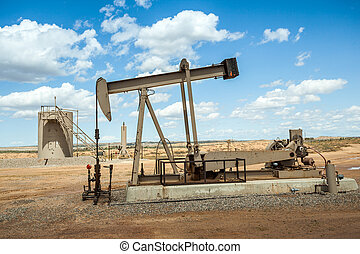 Oil pump jack surrounded by flat desert