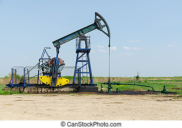 Oil Well Machine in Field on Clear Sunny Day, horizontal shot