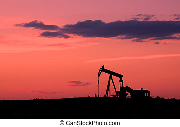 an oil pumpjack silhouetted against a colorful sunset