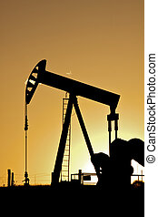 an oil pumpjack silhouetted in the sunset