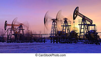 oil pumps at sunset sky background. panorama.