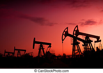 Oil pumps at sunset sky background. Selective focus, shallow depth of field.