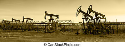 Pump jack group and wellheads. Extraction of oil. Toned.