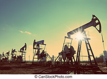 oil pumps silhouette against sun - vintage retro style