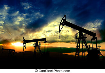 Oil pumps jack. Oil industry equipment working on sunset background