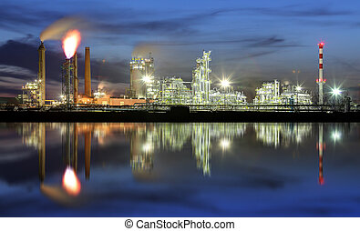 Oil refinery at night with reflection in water