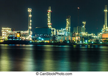 Oil refinery at night with shadow in river