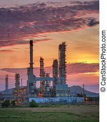 Oil refinery factory along twilight sky