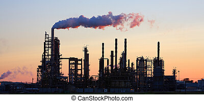Oil Refinery - Oil refinery with smoke billowing at sunset.