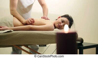 Oil relaxation massage for back. Man rubs sesame oil for young female, slider