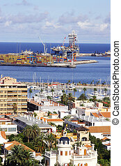 Oil Rig and Town - Oil rig docked at quay behind typical...