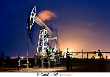 Oil Rig at night. - Oil pump-jack in action. Gas torches. ...
