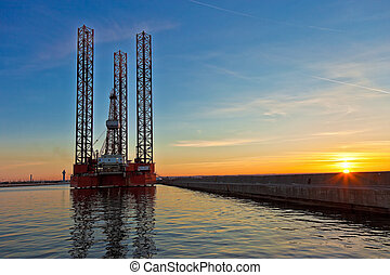 Oil rig at sunset background.