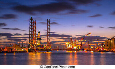 Oil Platforms being built in a manufacturing harbor under beautiful sunset