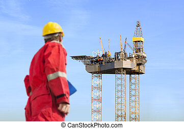 Oil rig construction - Roughneck (out of focus) looking at a...