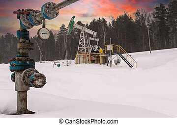 Oil rig energy industrial machine for petroleum in the sunset background for design. Oil pumpjack winter working. Oil pump under the sunrise sunset sky. Oil pressure gauge shows 3,5 MPa