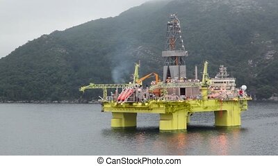 Oil rig located in sea near coastline with forest on mountain under cloudy sky