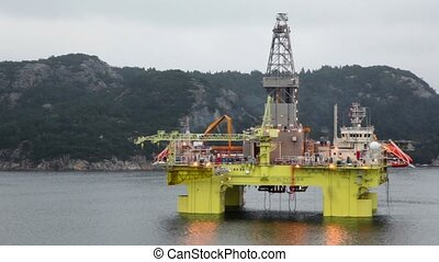Oil rig located in sea near shore with forest on mountain